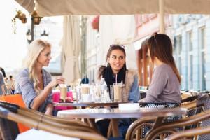 Frauen im Cafe an einem Tisch ansprechen